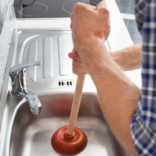 Closeup Of Man Using Plunger In Kitchen Sink
