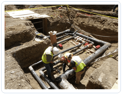 plumbers in trench with pipelines