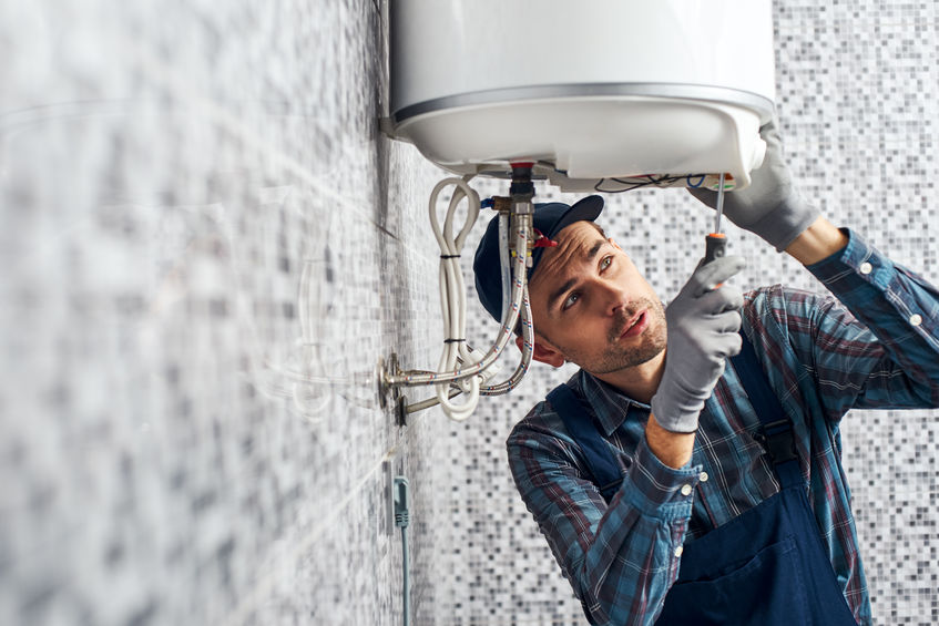 Worker set up electric heating boiler at home. Close-up of young handyman